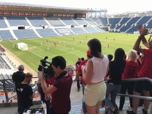 Stadium Scene with a woman filming inside the section